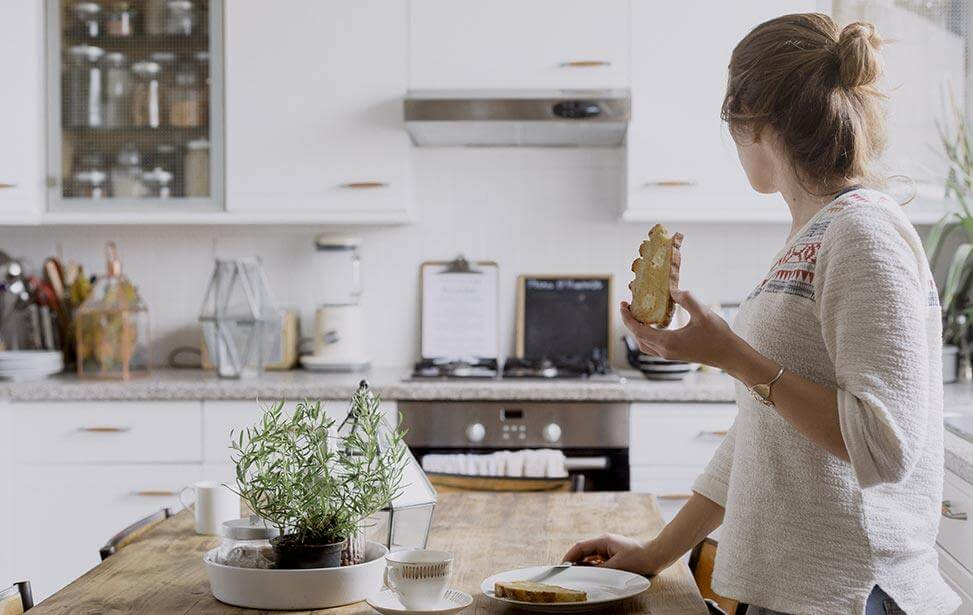 woman in kitchen eating toast